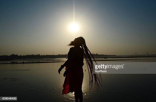 An indian naga sadhu dries up his hairs after taking a holy dip at sangam confluence of three great rivers GangesYamuna and mythical saraswatiduring...