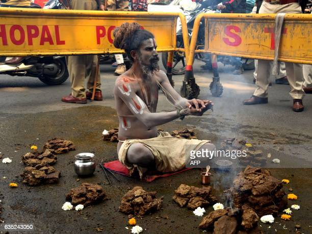 An Indian Naga Sadhu performs a prayer ritual as he sits with others in front of police barricades in Bhopal on February 14 during a roadside protest...
