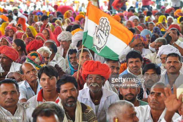 TOPSHOT An Indian National Congress party supporter looks up to a Congress party flag during an election rally in Bandanwara in the Indian state of...