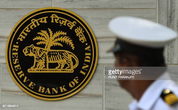 An Indian naval officer walks past the logo of India's central bank the Reserve Bank of India in Mumbai on November 9 2016 Indian Prime Minister...