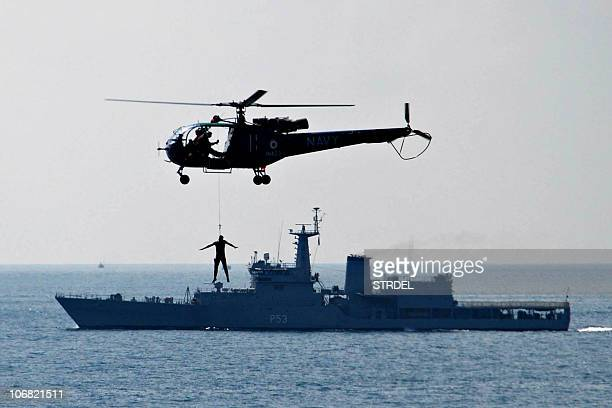 An Indian Navy Chetak helicopter demonstrates a search and rescue mission as the destroyer INS Ranjit sails in the background in the waters off the...