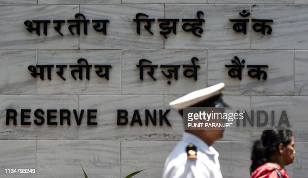 An Indian navy officer walks past the entrance of the Reserve Bank of India head office in Mumbai on April 4 2019 India's central bank cut interest...