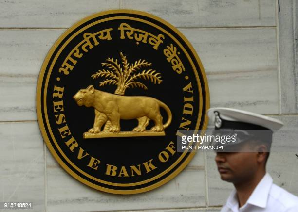 An Indian navy officer walks past the entrance of the Reserve Bank of India head office in Mumbai on February 7 2018 India's central bank kept...