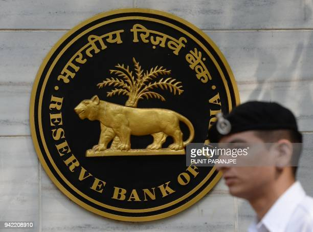 An Indian navy officer walks past the entrance of the Reserve Bank of India head office in Mumbai on April 5 2018 India's central bank on April 5...