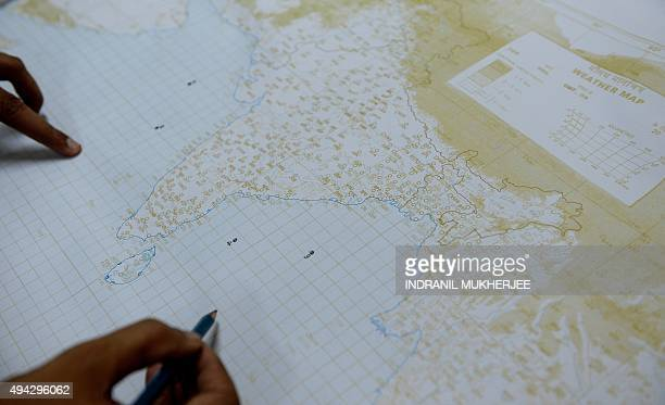 An Indian Navy sailor marks moored buoys used to detect a tsunami around the Indian peninsula on a map during the testing of a Tsunami Early Warning...