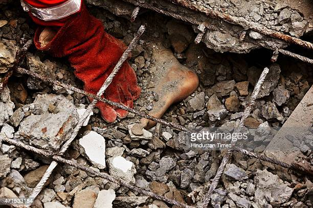 An Indian NDRF team member trying to remove the boulders from a body trapped inside debris during a rescue operation near Sobhabhawati Bridge four...