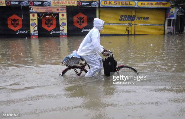 An Indian newspaper distributor pedals his bicycle through a flooded street during a heavy downpour in Agartala in the northeastern state of Tripura...
