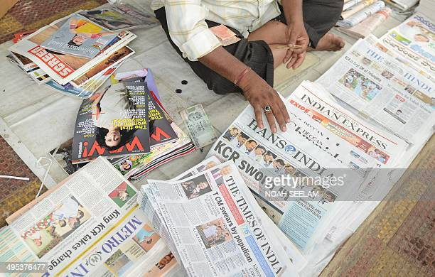 An Indian newspaper vendor sorts papers reporting on the newlyformed Telangana state's first Chief Minister K Chandra Sekhar Rao taking office in...