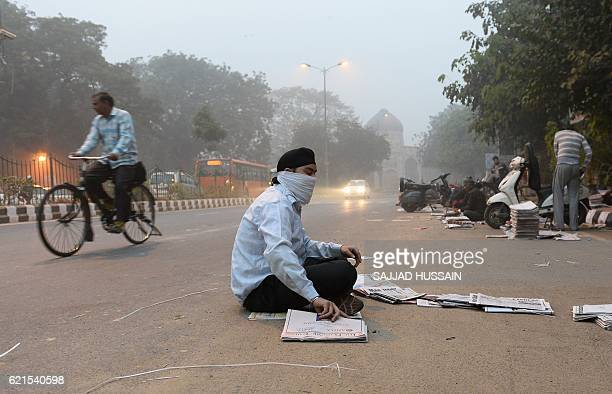 An Indian newspaper vendor wears a mask whilst he sorts news papers on a road as heavy smog covers New Delhi on November 7 2016 Schools in the Indian...