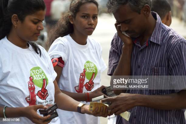 An Indian NGO volunteer distributes packets of condoms to a passerby at street corner on the occasion of World Aids Day in Mumbai on december 1 2017...