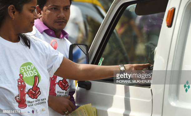 An Indian NGO volunteer distributes packets of condoms to a passing driver at street corner on the occasion of World Aids Day in Mumbai on december 1...