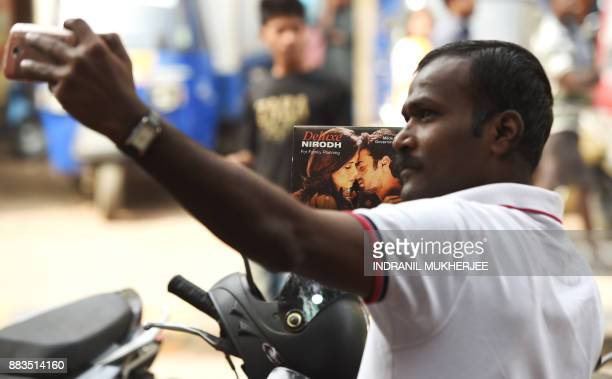 An Indian NGO volunteer takes a selfie with a box of condoms during a distributuion drive at a street corner on the occassion of World Aids Day in...