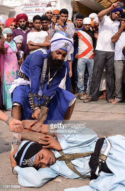 An Indian Nihang a religious Sikh warrior shows his skill in the Sikh martial art known as 'Gatka' during a religious procession near the Golden...