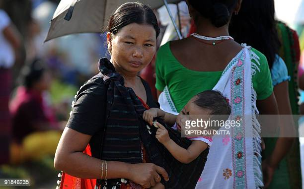An Indian Nishi tribeswomen carries her child as she queues to cast her vote at a polling station in the village of Kiming some 30kms froms Itanagar...