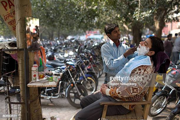 An Indian office worker gets a shave from a barber in a motorcycle parking lot in Nehru Park New Delhi India February 4 2008 Sales of motorcycles in...