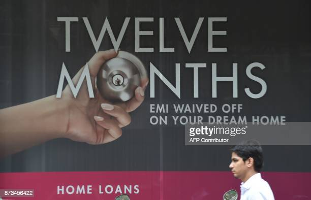 An Indian office worker walks past an advertisement for a home loan outside a bank in Mumbai on November 13 2017 According to figures released by the...
