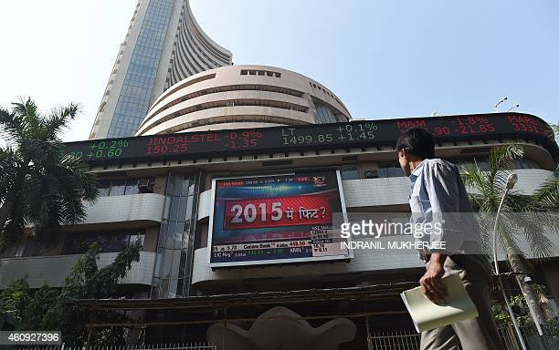 An Indian officegoer walks outside the Bombay Stock Exchange watching share prices on a digital broadcast on its facade in Mumbai on December 31 2014...