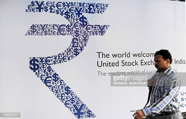 An Indian officegoer walks past a collage of the new Indian rupee symbol made with signs of the US dollar the yen the pound and the euro outside the...