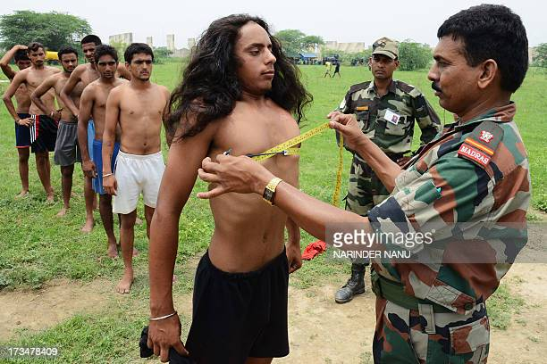 An Indian officers measures a candidate during a physical fitness test at an Indian Army recruitment rally at Khasa some 15 Kms from Amritsar on July...