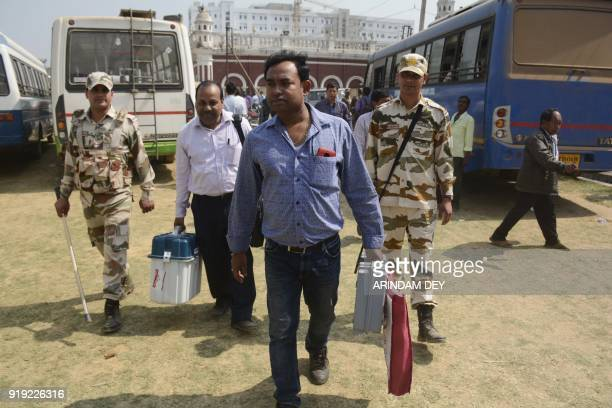 An Indian official recruited for election duty carries an Electronic Voting Machine walks towards the polling station on the eve of the Tripura state...