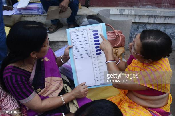 An Indian official recruited for polling duties inspects voting materials ahead of legislative assembly election in Agartala the capital of...