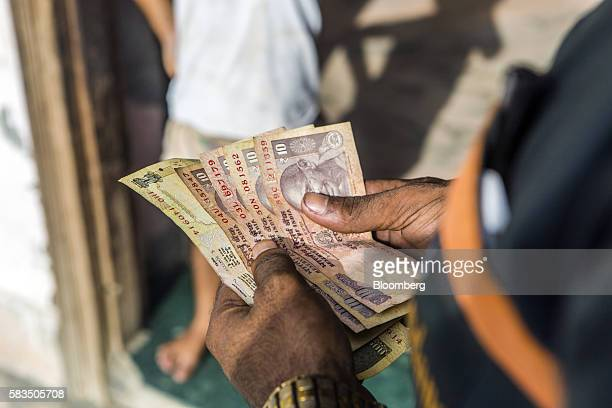 An Indian Oil Corp employee counts Indian rupee banknotes during the delivery of liquefied petroleum gas cylinders in the village of Mangrauli Uttar...