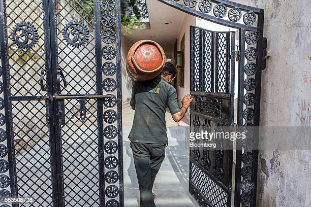 An Indian Oil Corp employee delivers a liquefied petroleum gas cylinder in the village of Mangrauli Uttar Pradesh India on Tuesday July 19 2016...