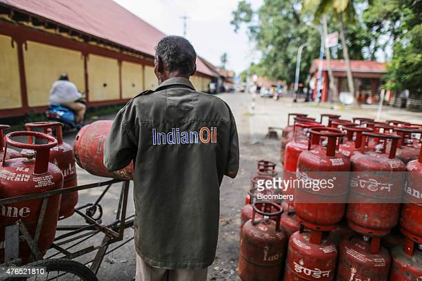 An Indian Oil Corp employee loads liquid petroleum gas cylinders onto his vehicle in Cochin India on Friday May 29 2015 Prime Minister Narendra Modi...
