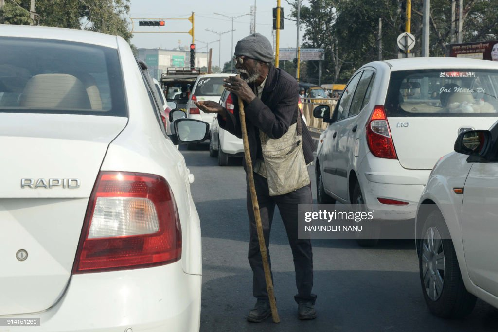 An Indian old man begs at a the roadside in Amritsar on February 4 2018 / AFP PHOTO / NARINDER NANU