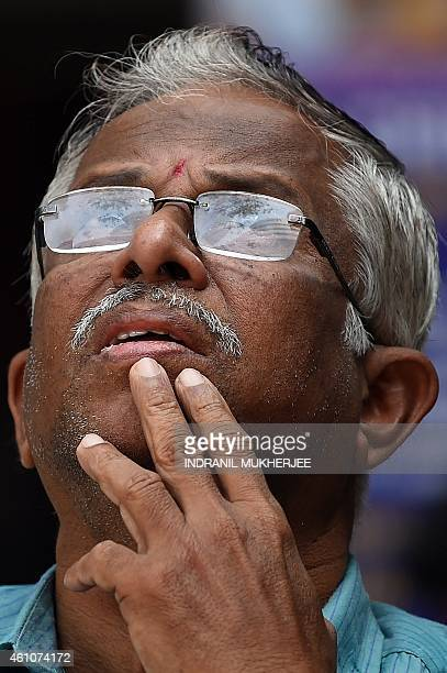 An Indian onlooker watches share prices on a digital broadcast on the facade of the Bombay Stock Exchange in Mumbai on January 6 2015 The BSE 30...