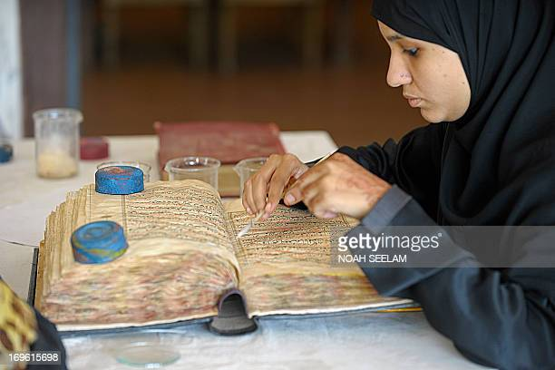 An Indian paper conservator restores an antique copy of the Koran at Chowmahalla Palace in Hyderabad on May 29 2013 Some 300 antique copies of the...