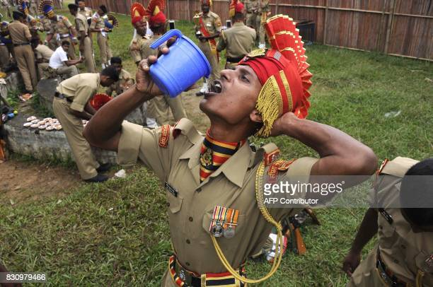 An Indian paramilitary drinks water after marching during the final dress rehearsal ahead of Independence Day celebrations in Agartala the capital of...