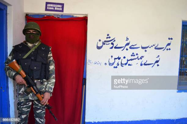 An Indian Paramilitary force personal stands guard outside a polling station in central kashmir's Budgam district during ByPolls of Indian...