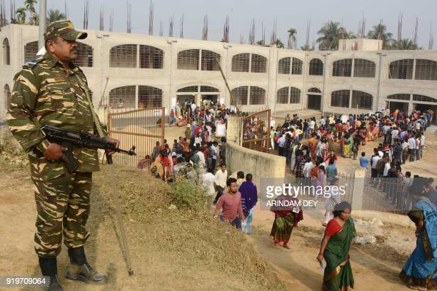 An Indian paramilitary force personnel stands guard at a polling station during Tripura legislative assembly elections in Agartala the capital of...