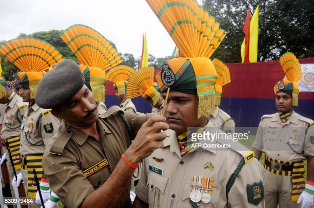 An Indian paramilitary officer adjusts the head gear of a colleague during the final dress rehearsal ahead of Independence Day celebrations in...