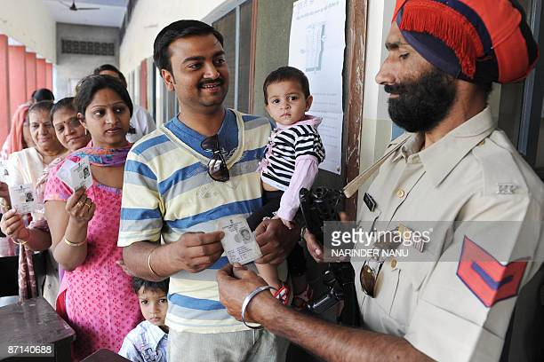 An Indian paramilitary soldier checks voters identity cards as they stand in a queue to cast their votes at a polling station in Amritsar on May 13...