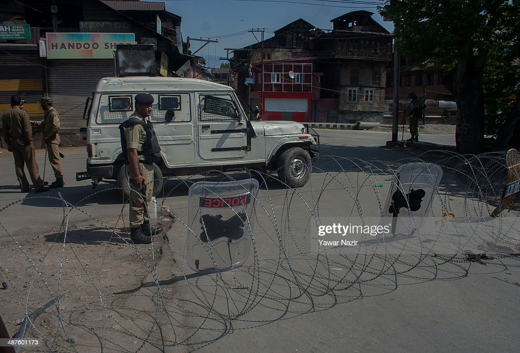 An Indian paramilitary soldier guards a deserted road during a curfew following a killing of a youth on May 01, 2014 in Srinagar, the summer capital of Indian-administered Kashmir, India. Kashmir remained on boil a day after a youth was shot dead by Indian armed government forces in the Old City of Srinagar. Two persons including a woman were also wounded when Indian forces fired at Kashmiri stone hurling protesters who were shouting 'down with India' slogans. The Indian forces in Kashmir clamped a stringent curfew in the region to stop anti-India protests from escalating while as a shutdown was observed to protest the killing of the youth.