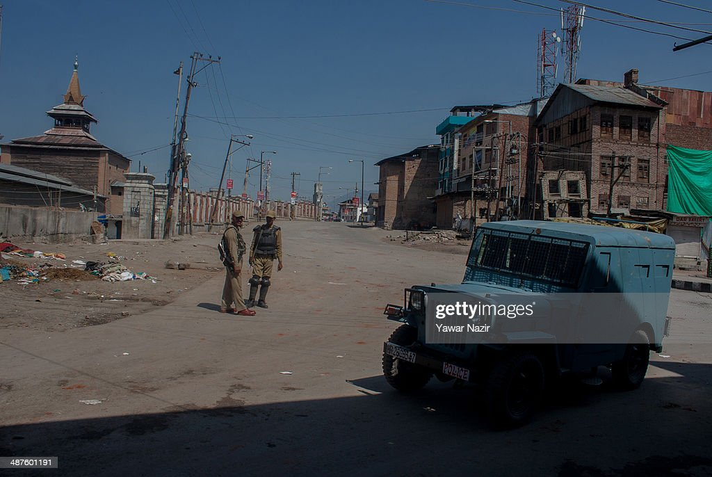 An Indian paramilitary soldier guards a deserted road in the old city during a curfew following a killing of a youth on May 01, 2014 in Srinagar, the summer capital of Indian-administered Kashmir, India. Kashmir remained on boil a day after a youth was shot dead by Indian armed government forces in the Old City of Srinagar. Two persons including a woman were also wounded when Indian forces fired at Kashmiri stone hurling protesters who were shouting 'down with India' slogans. The Indian forces in Kashmir clamped a stringent curfew in the region to stop anti-India protests from escalating while as a shutdown was observed to protest the killing of the youth.