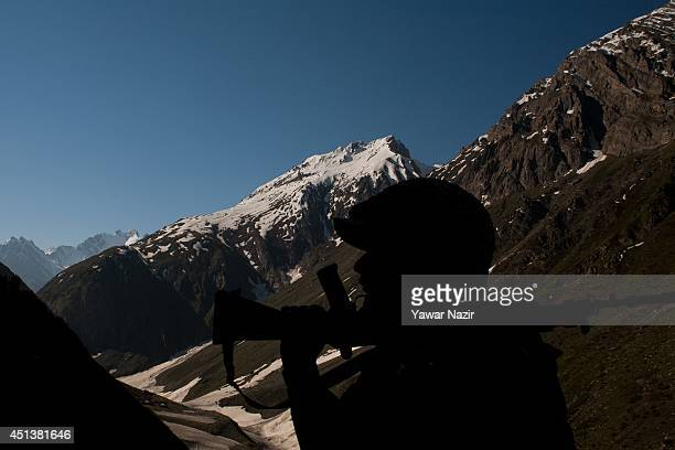 An Indian paramilitary soldier is silhouetted against the snow capped mountain as he guards during Hindu pilgrimage to the sacred Amarnath Cave one...