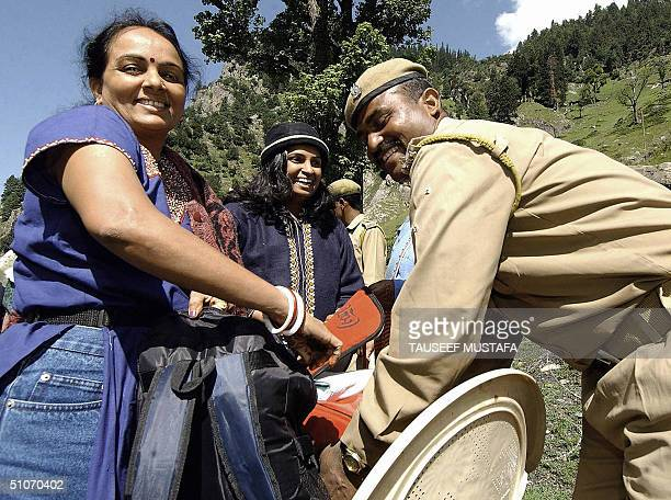 An Indian paramilitary soldier searches the bags of a female Hindu pilgrim in the village of Chandanwari some 114kms south of Srinagar.15 July 2004....