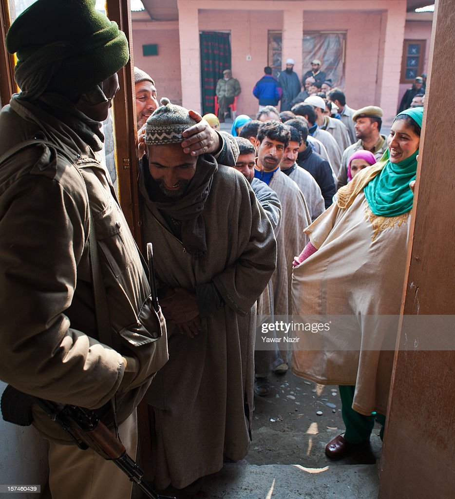 An Indian paramilitary soldier stands guard as Kashmiri Muslim village heads wait in queues to enter polling station to cast their vote during state's legislative council election on December 03, 2012 in Budgam, west of Srinagar, Indian Administered Kashmir. Village heads in Indian-administered Kashmir voted for their representatives in the state's legislative council after 38 years today. These grass root workers are represented by four people in the council- the lower house of Kashmir assembly. This year the village heads were attacked by unidentified gunmen in the conflict torn region. Many resigned from their post after at least 10 village heads were killed in attacks. Today's polling saw long queues despite the resistance leadership calling for a boycott. But the biggest militant group in the region- the Hizbul Mujahideen- had refrained from calling a boycott saying the polling was necessary for daily administration of the state.