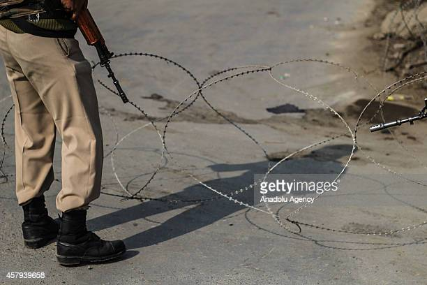 An Indian paramilitary soldier stands guard at a temporary check point during restrictions in parts of Old City of Srinagar Jammu and Kashmir India...