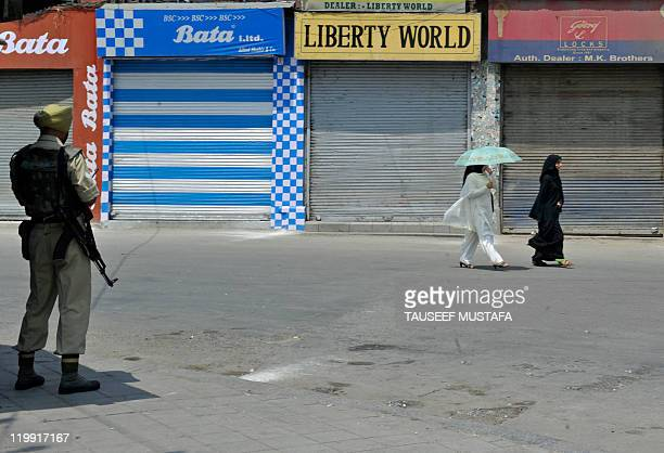 An Indian paramilitary soldier stands guard in a street as Kashmiri women pass by during a strike which followed the alleged rape of a married woman...