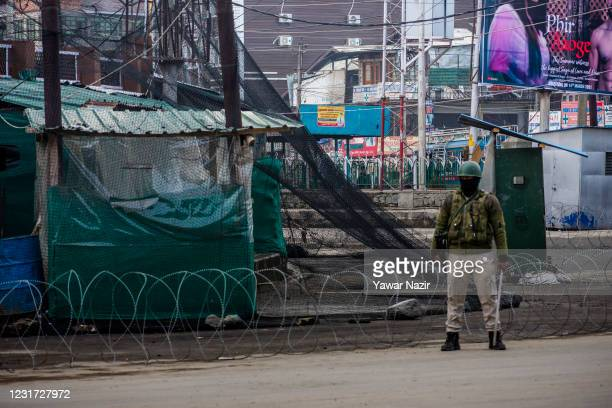 An Indian paramilitary soldier stands guard in front of his bunkers on a main road, on March 15, 2021 in Srinagar, the summer capital of Indian...