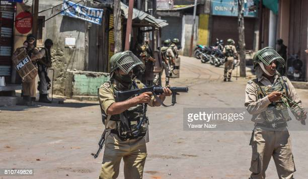 An Indian paramilitary trooper aims his tear gas rifle at Kashmiri Muslim protesters during a protest after Kashmiri Muslims defied curfew on the the...