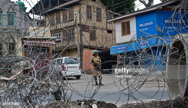 An Indian paramilitary trooper guards the deserted main road during a curfew following violence that has left over 36 people dead and thousands...