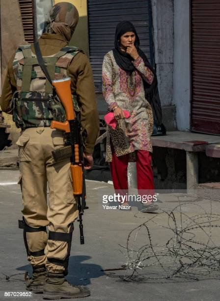 An Indian paramilitary trooper look towards a Kashmiri Muslim woman walking on a deserted road during a strike on October 27 2017 in Srinagar the...