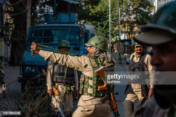 An Indian paramilitary trooper shoots stones with his catapult at Kashmiri Muslim protesters during a protest against the killing of a Kashmiri rebel...