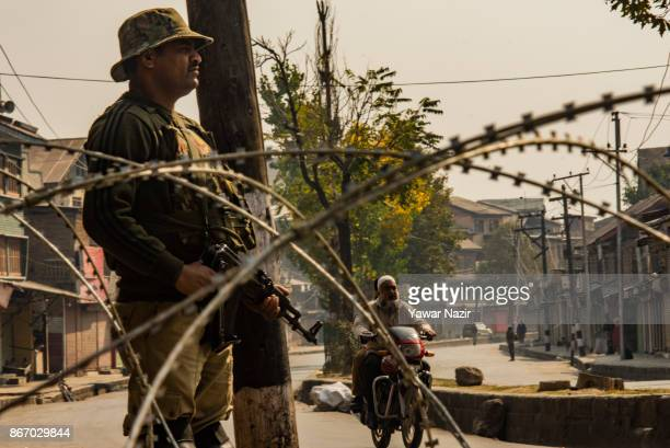 An Indian paramilitary trooper stands alert as a Kashmiri motorcyclist crosses a deserted road during a strike on October 27 2017 in Srinagar the...