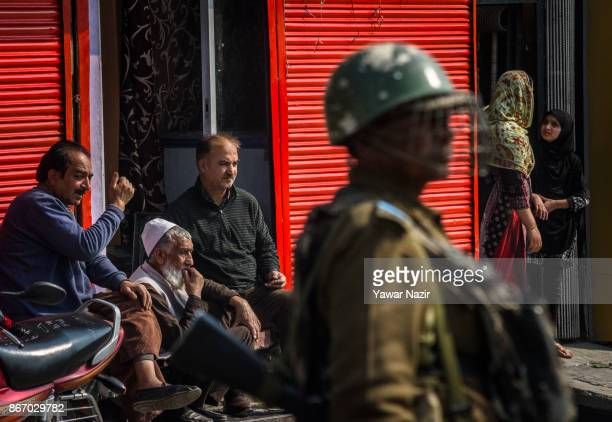 An Indian paramilitary trooper stands alert as Kashmiri Muslims rest on the porch of shuttered shops during a strike on October 27 2017 in Srinagar...
